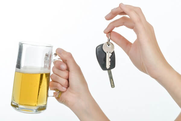 A person holding a glass of beers and car keys.